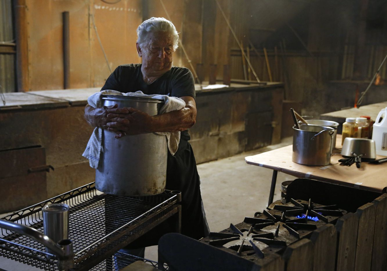 Tootsie Tomanetz lifts a large pot of water and beans to a gas burner.