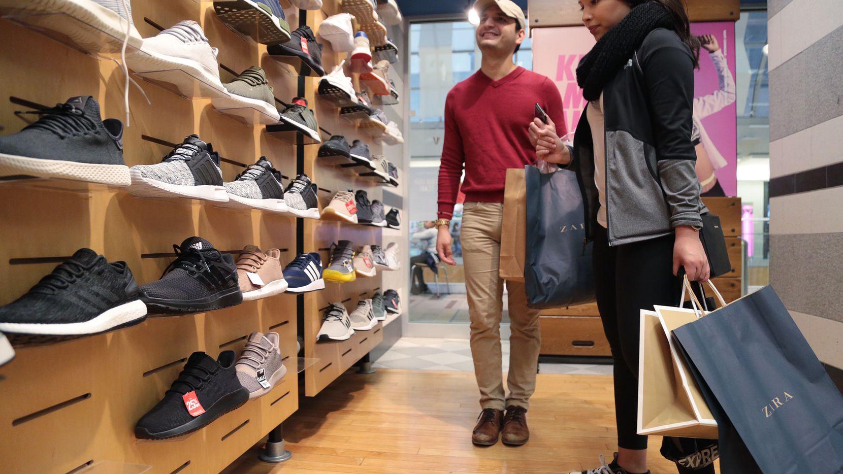 Mark Jiménez y Julie Aguilar compran zapatos en una tienda del Galleria Mall, el viernes por la tarde. MARIA OLIVAS/ ESPECIAL PARA AL DIA