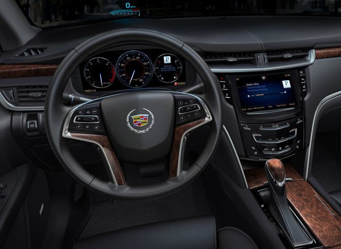 Interior of the 2013 Cadillac XTS showing the CUE system and widescreen LED dashboard.