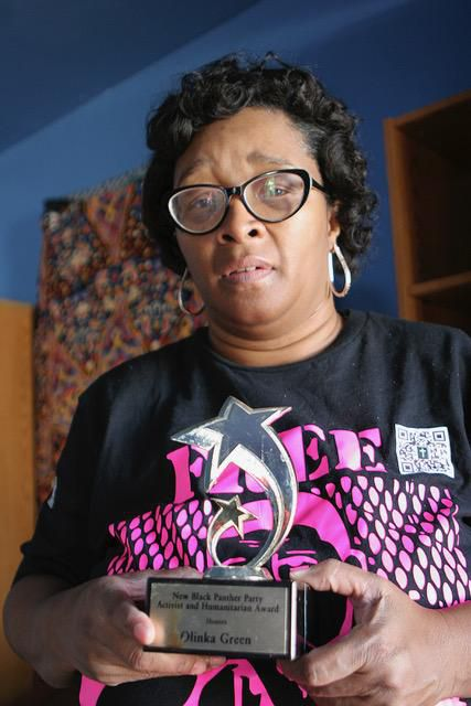 Green holds her award for activism and humanitarianism from the New Black Panther Party.