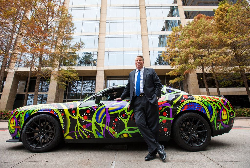 Chairman and CEO Clifford Fischer poses for a portrait next to his custom wrapped 2015 Dodge Challenger Hellcat, which is one of his collection of expensive vehicles, on Wednesday, December 6, 2017 outside Fischer headquarters in Dallas. (Ashley Landis/The Dallas Morning News)