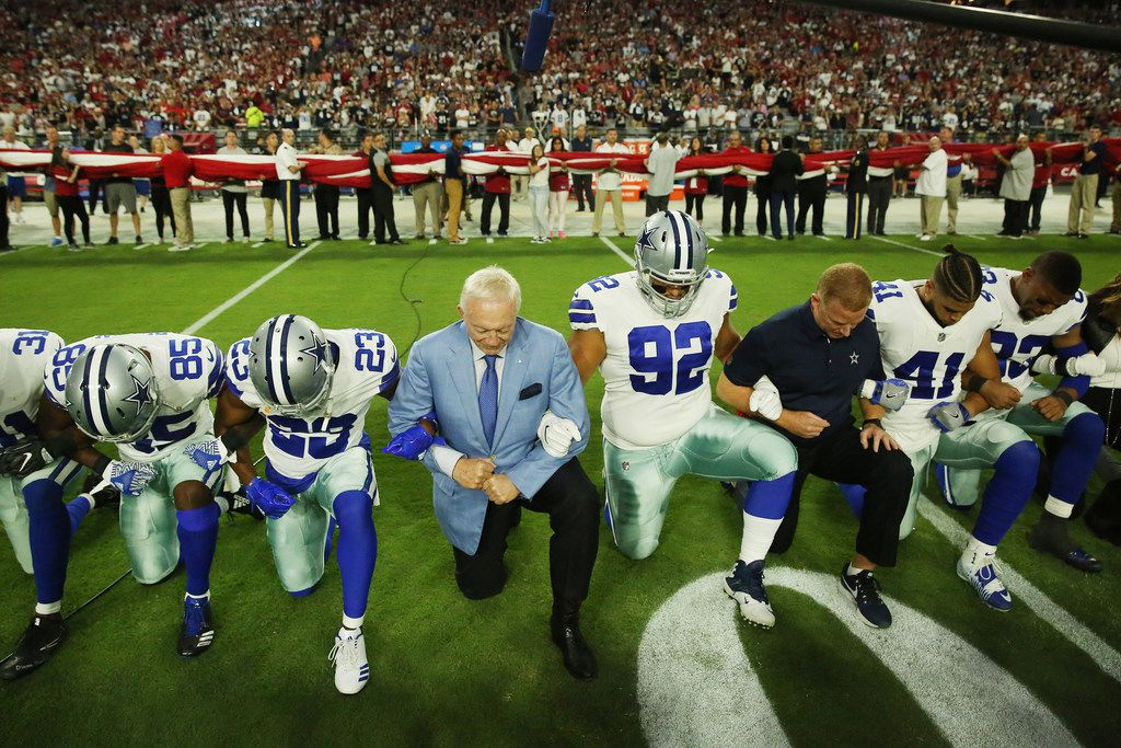 Dallas Cowboys players and staff, including owner Jerry Jones and head coach Jason Garrett, took a knee before the playing of the national anthem Monday night. (Andy Jacobsohn/Staff Photographer)