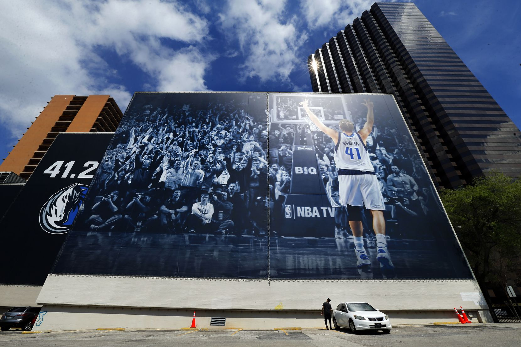 """A young man stands by a 68-by-193-foot mural of Dallas Mavericks forward Dirk Nowitzki before driving away from the YMCA building in downtown Dallas on March 24, 2019. The Mavericks say it's an augmented reality wall where """"Dirk comes to life on your smartphone with 21 shots from all 21 of his historic seasons."""" The wallscape will be active through April 13."""