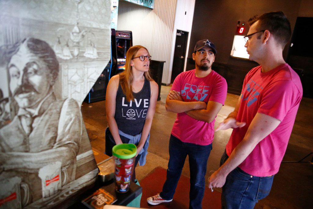 Lauren Featherstone (from left) talks to Orlando Tijerina, technician, and her coach Chris Delp before attempting to break the world record for the classic arcade game Tapper at Free Play in Arlington, TX on July 14, 2017.