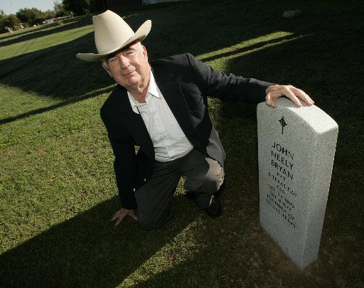 In this 2006 file photo, John Neely Bryan kneels by the headstone that will be dedicated Saturday at the Austin State Hospital Cemetery in Austin.