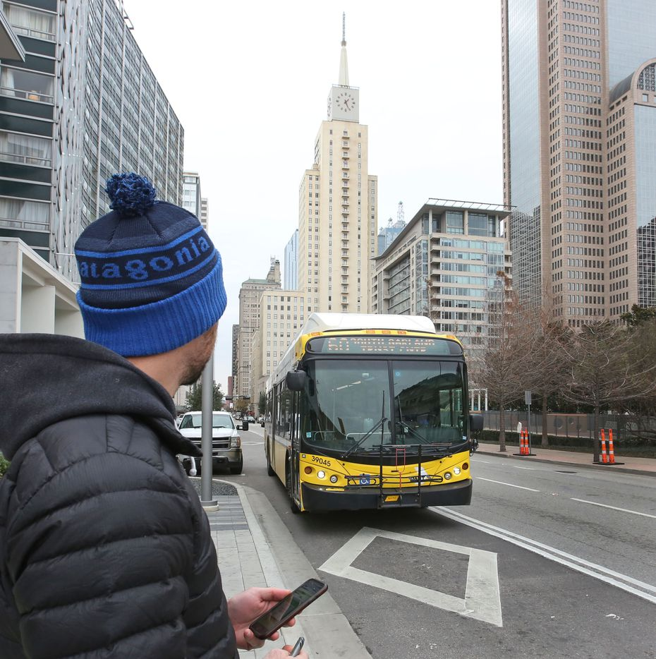 Brendan Meyer catches the bus on Commerce Street in front of The Dallas Morning News office as he commutes via mass transit from the downtown office to the Dallas Arboretum.
