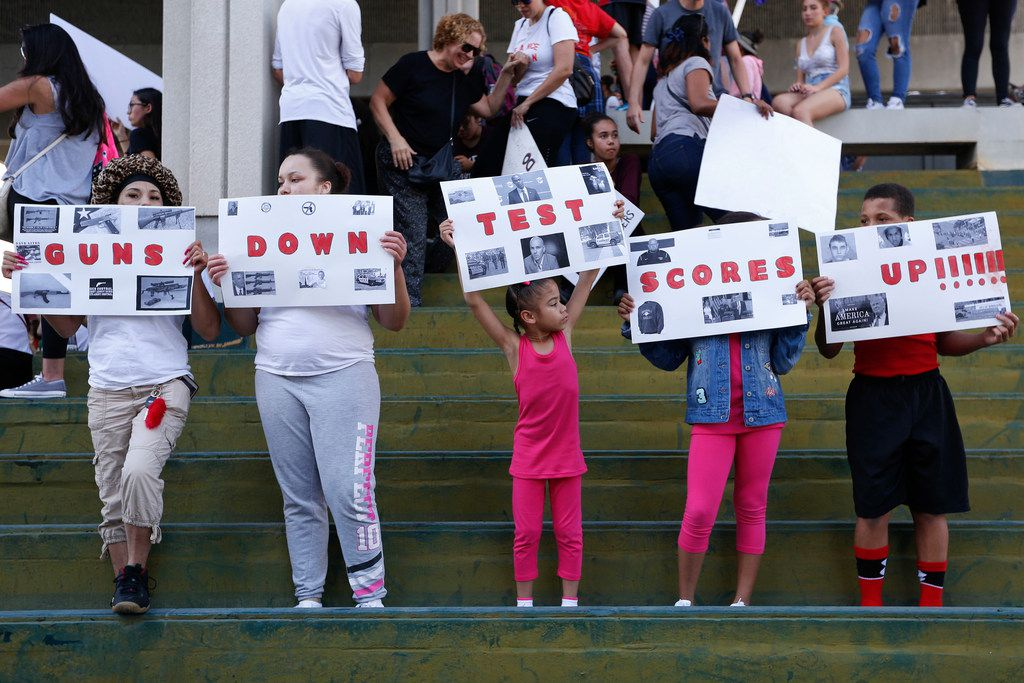 A group of people hold signs that read 'Guns Down Test Scores UP' during a protest against guns on the steps of the Broward County Federal courthouse in Fort Lauderdale, Fla., on Saturday. Nikolas Cruz, a former student, is charged with killing 17 people at Marjory Stoneman Douglas High School in Parkland, Fla., on Wednesday.