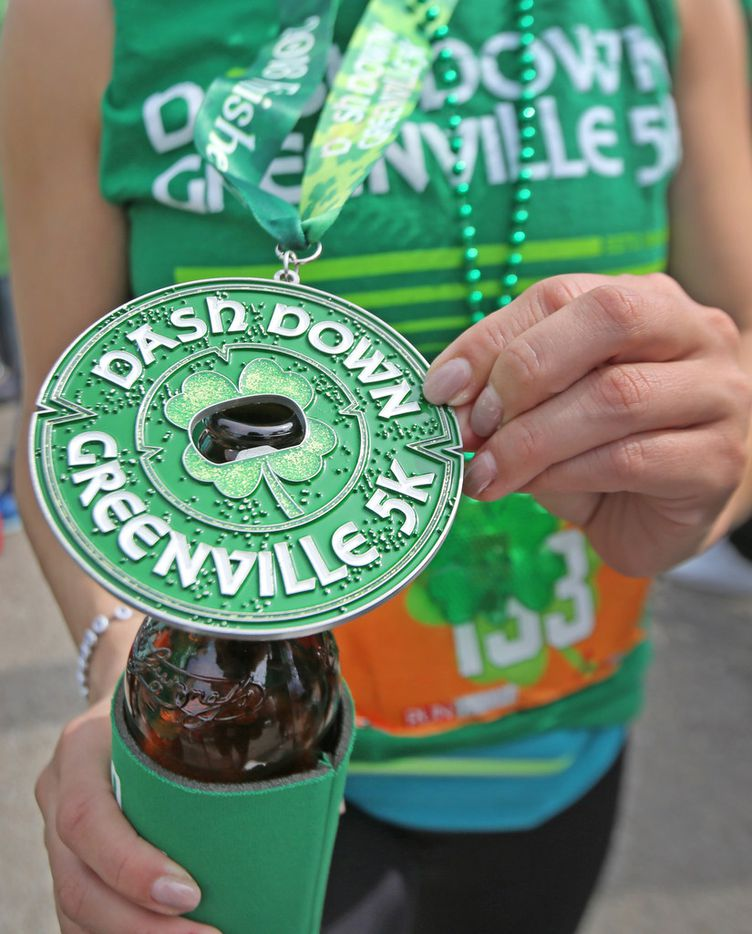 "The medal given finishers of the ""Dash Down Greenville 5K"" doubles as a bottle opener, as seen during the Dallas St. Patrick's Parade & Festival along Greenville Avenue in Dallas on Saturday."