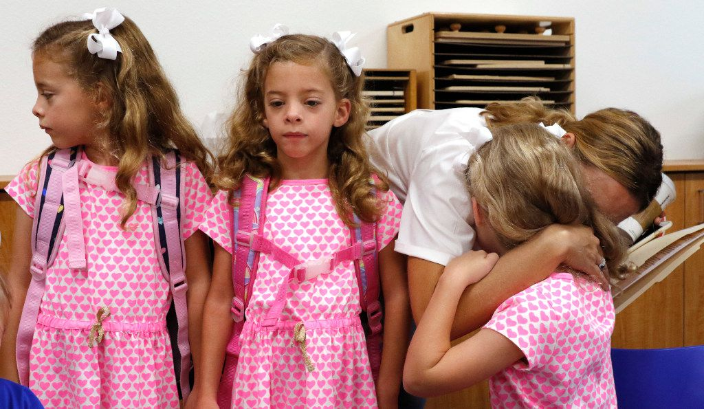 From left: Six-year-old triplets Emma, Chloe and Rosie Gilmore got hugs from their mother, Anna Gilmore, on the first day of school Monday at University Park Elementary School.