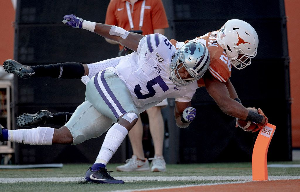Texas running back Keaontay Ingram (26) scores a touchdown as Kansas State linebacker Da'Quan Patton (5) tries to knock him out of bounds during an NCAA college football game Saturday, Nov. 9, 2019, in Austin, Texas. (Nick Wagner/Austin American-Statesman via AP)