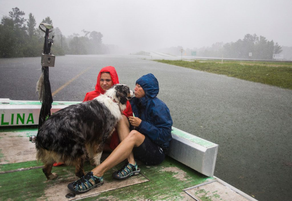 Averie and Sybrena Brakin comfort their dog, Dallas, as they are taken by airboat to safety as waters rise from Hurricane Harvey on Wednesday, August 30, 2017 in Lumberton, Texas. (Ashley Landis/The Dallas Morning News)