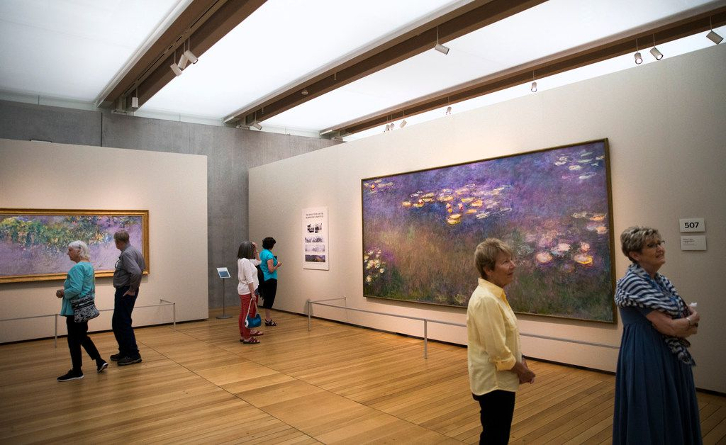 "Museum-goers view  ""Water Lilies"" paintings by Claude Monet as part of the Monet: The Late Years exhibit at the Kimbell Art Museum."
