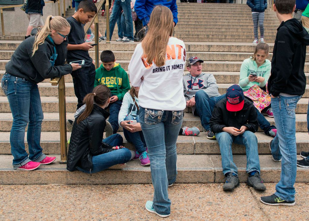 A group of teens check their smartphones outside the Natural History Museum in Washington.