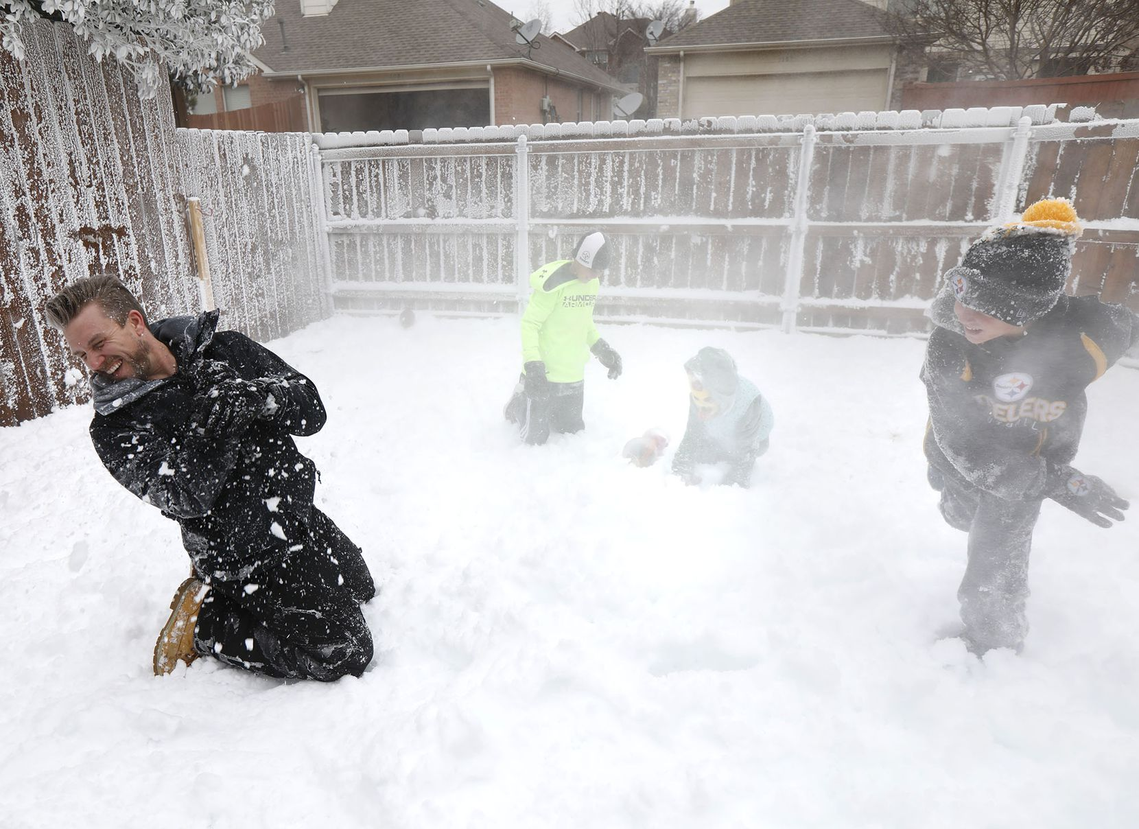 Jeramy Melchiorre (left), gets hit with a snowball thrown by his son, Christian Melchiorre, 9, while his son Jude Melchiorre, 12, and his niece, Emmaline Gibson, 6, play in a winter wonderland he created using a power washer  that blows freezing water the makes snow in their Allen backyard.