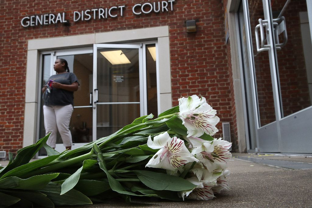 """CHARLOTTESVILLE, VA - AUGUST 14:  Flowers are left outside the Charlottesville General District Court before a scheduled appearance via video link for James Alex Fields Jr. August 14, 2017 in Charlottesville, Virginia. Fields has been charged with second degree murder, malicious wounding, and failure to stop in an accident resulting in death following an incident where a vehicle plowed into a crowd of counter protesters during the """"Unite the Right"""" rally on August 12, 2017. 32 year old Heather Heyer was killed in the incident.  (Photo by Win McNamee/Getty Images)"""