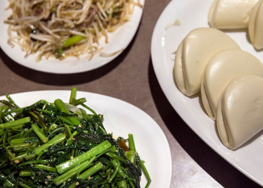 Water spinach, a seasonal green sautéed with garlic, is a good addition to the feast.