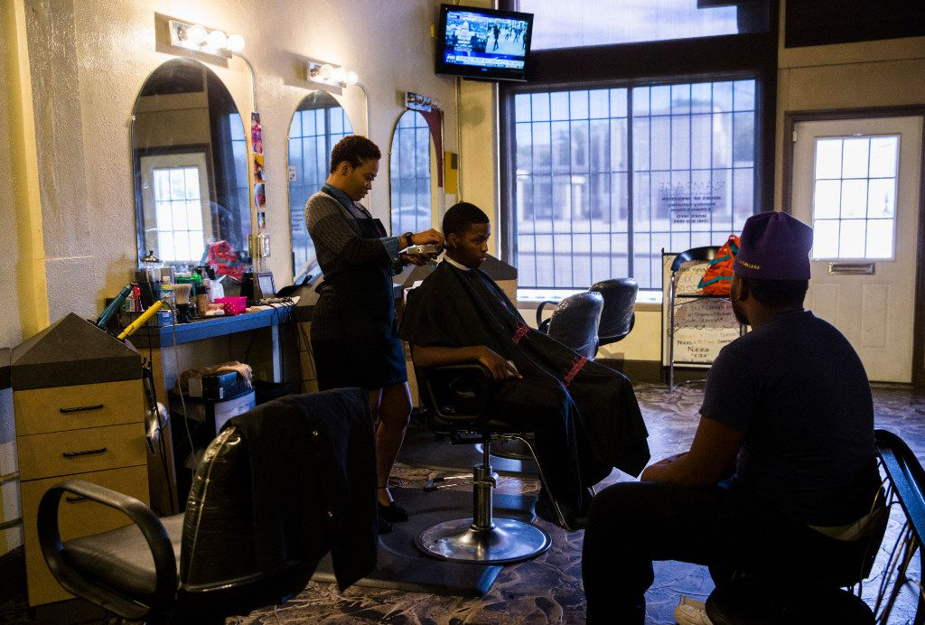 Fabian Jones, left, gives a hair cut to Jacorian Miller while Robert Hampton IV waits his turn at Rampage Beauty and Barber Salon across the street from Fair Park on Friday, January 20, 2017 on Parry Avenue in Dallas.