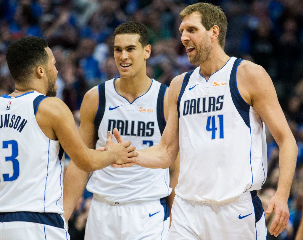 Dallas Mavericks forward Dirk Nowitzki (41) celebrates with guard Jalen Brunson (13) and forward Dwight Powell (7) after passing Wilt Chamberlain for the 6th NBA all-time scoring record during the first quarter of an NBA game between the Dallas Mavericks and the New Orleans Pelicans on Monday, March 18, 2019 at American Airlines Center in Dallas. (Ashley Landis/The Dallas Morning News)