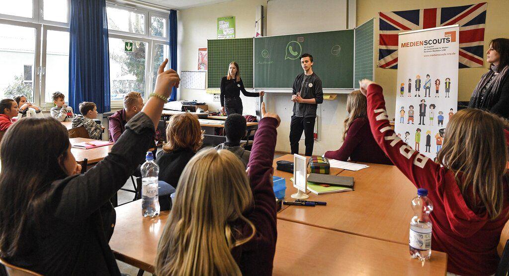 Los instructores Leon Sielinski (de pie, a la derecha) y Chantal Hueben imparten una clase sobre cómo manejarse en las redes sociales en Essen Alemania, el 18 de marzo del 2019. Alemania está a la vanguardia en el uso de adolescentes para enseñar a otros estudiantes los secretos del mundo digital. (AP Photo/Martin Meissner)