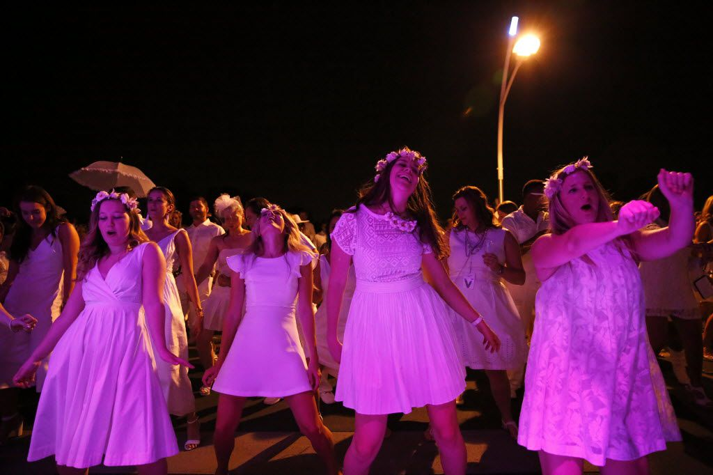 From left, Hope Duffie, Kamryn Hawrylak, Meredith Lockhart and Marcy Cook dance during the inaugural Diner en Blanc Dallas on the Continental Avenue Bridge in Dallas on Sept. 17, 2015. Exactly 1,678 people attended the event, which requires dinner guests to dress all in white and bring their own chairs and centerpieces. As per tradition, the location was kept private leading up to the event.