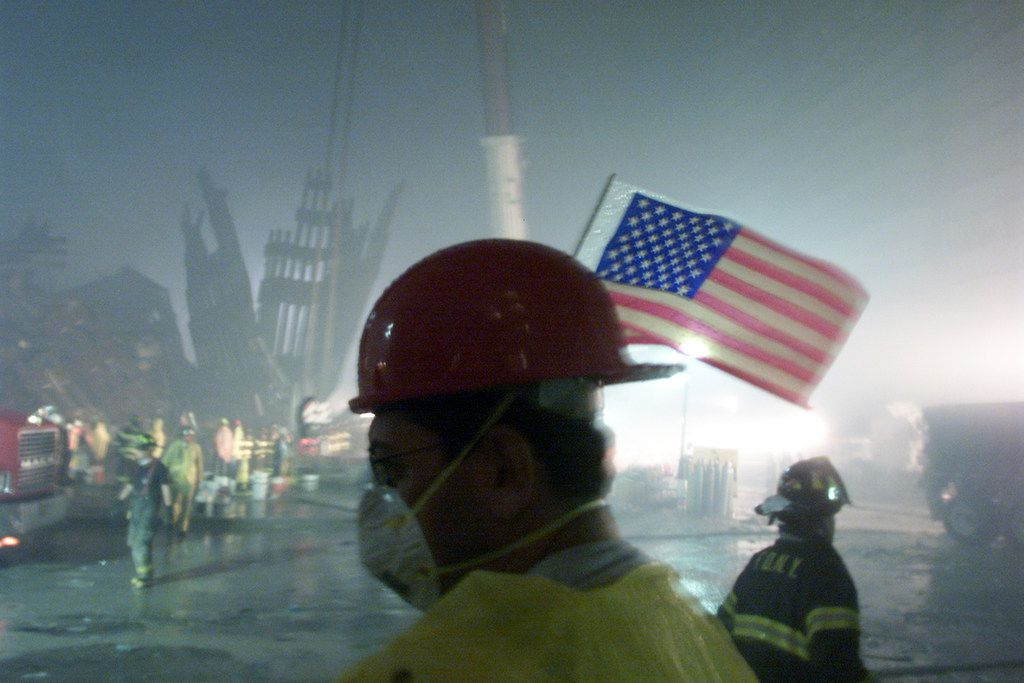 The remains of one of the World Trade Center towers provided a dreary backdrop for firefighters and other workers in the early morning hours of Sept. 14, 2001.