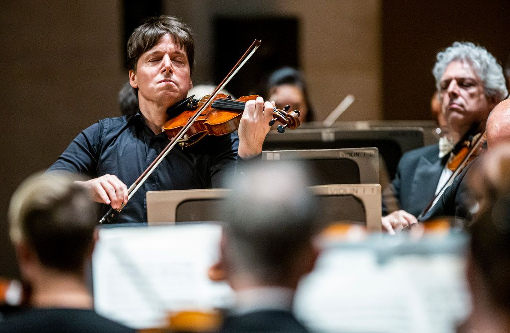 Joshua Bell (left), serves both as the first chair violinist and conductor during a Dallas Symphony Orchestra performance at the Meyerson Symphony Center.