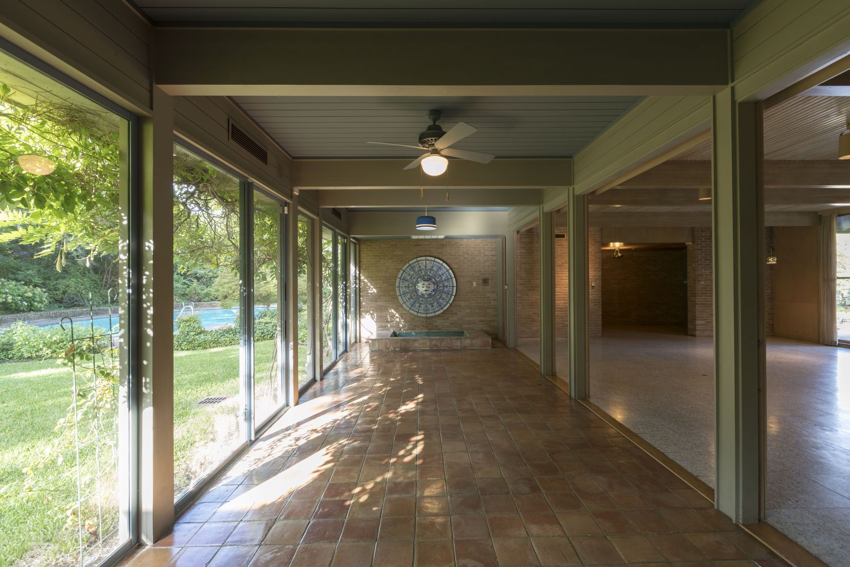 Floor-to-ceiling windows, terra cotta tile floors and covered verandas are signatures of O'Neil Ford's work.