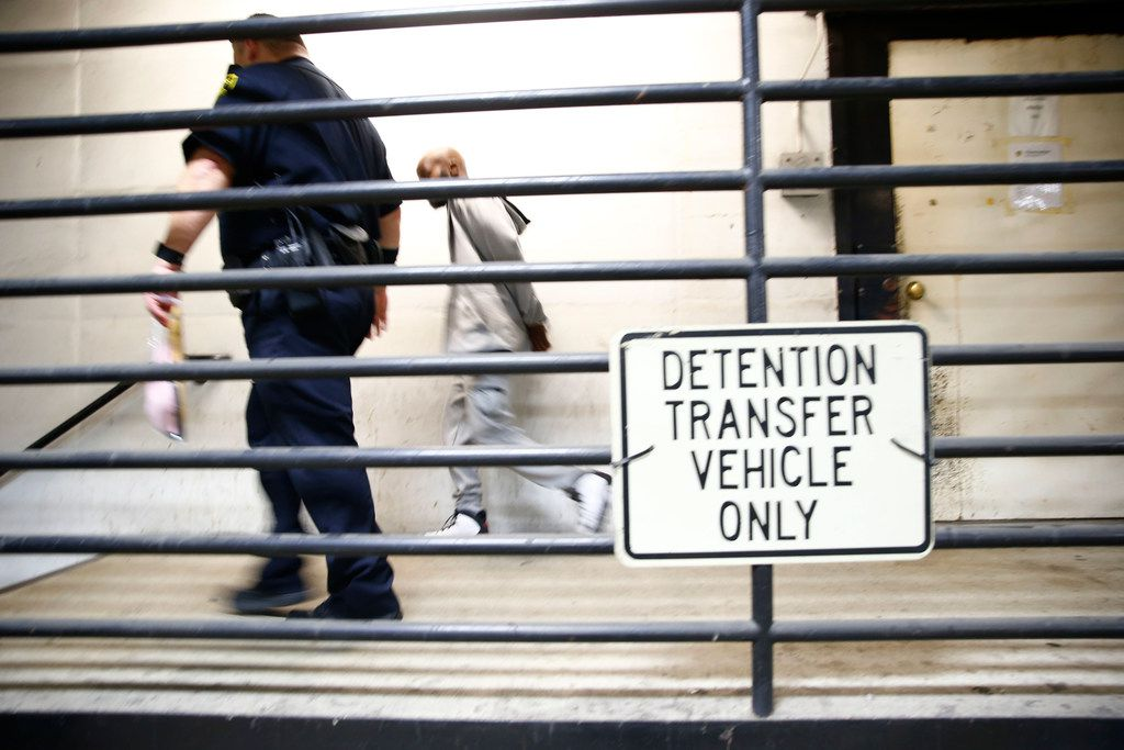 A prisoner escorted to the sally port of North Tower Detention Facility in the Lew Sterrett Justice Center in Dallas on Jan. 26, 2018. (Nathan Hunsinger/The Dallas Morning News)