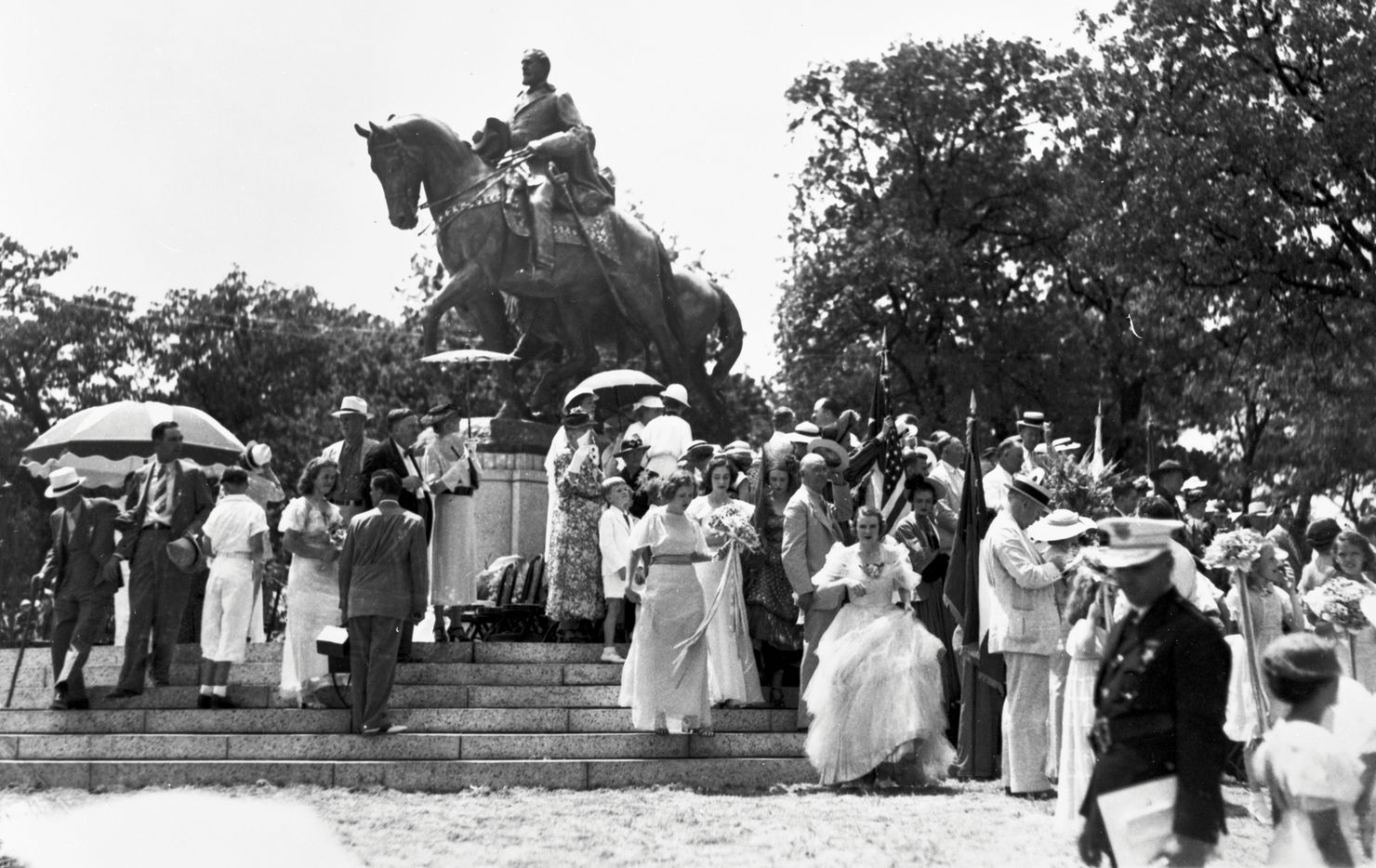 Dressed for a celebratory occasion, members of a crowd mill about the newly unveiled statue of Robert E. Lee after President Franklin D. Roosevelt dedicated it at Lee Park in Dallas, Texas, on June 12, 1936.