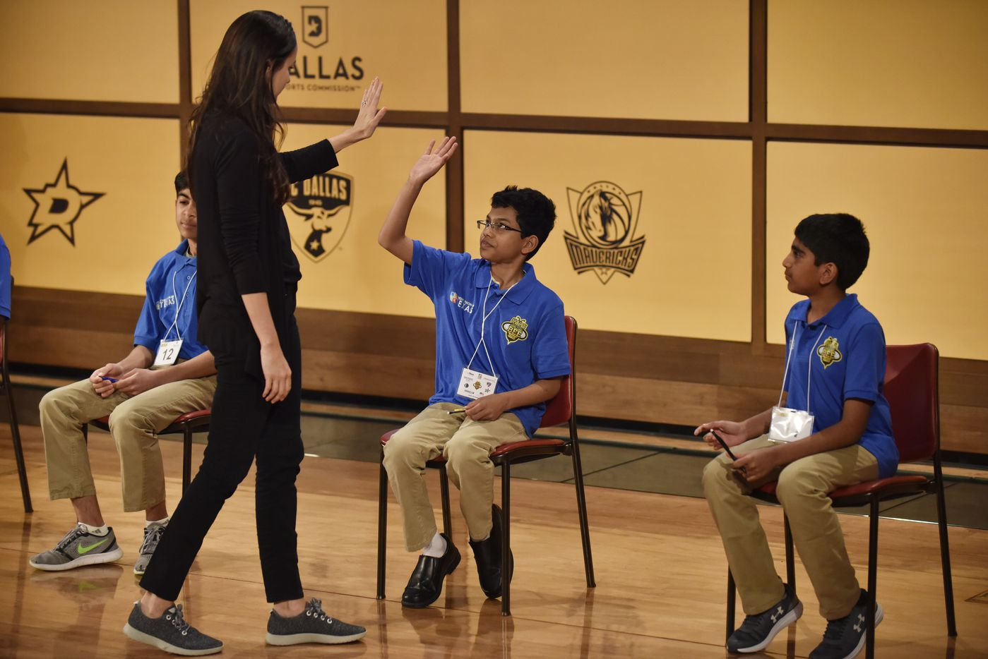 Sohum Sukhatankar, center, is one of four competitors given a high-five by a Stephanie Wilcox of WFAA after the final four completed a 25-word written test that served as the final round of the 61st annual Golden Chick Dallas Regional Spelling Bee at the George W. Bush Presidential Center on the campus of Southern Methodist University in Dallas, Saturday, March 09, 2019. Sukhatankar tied for second and will be advancing to the National Spelling Bee in Washington D.C. Abhijay Kodali, far-right, finished first earning a perfect score on the 25-word written test.