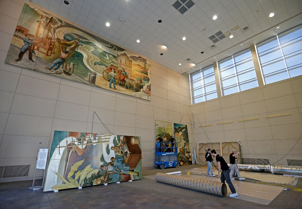 Workers from Unified Fine Arts work to remove the murals from the wall of the TXCN building  on Wednesday, March 15, 2017, in Dallas. The murals by nine artists including Perry Nichols will be taken to the Briscoe Center for American History on the University of Texas at Austin campus. (Jae S. Lee/The Dallas Morning News)
