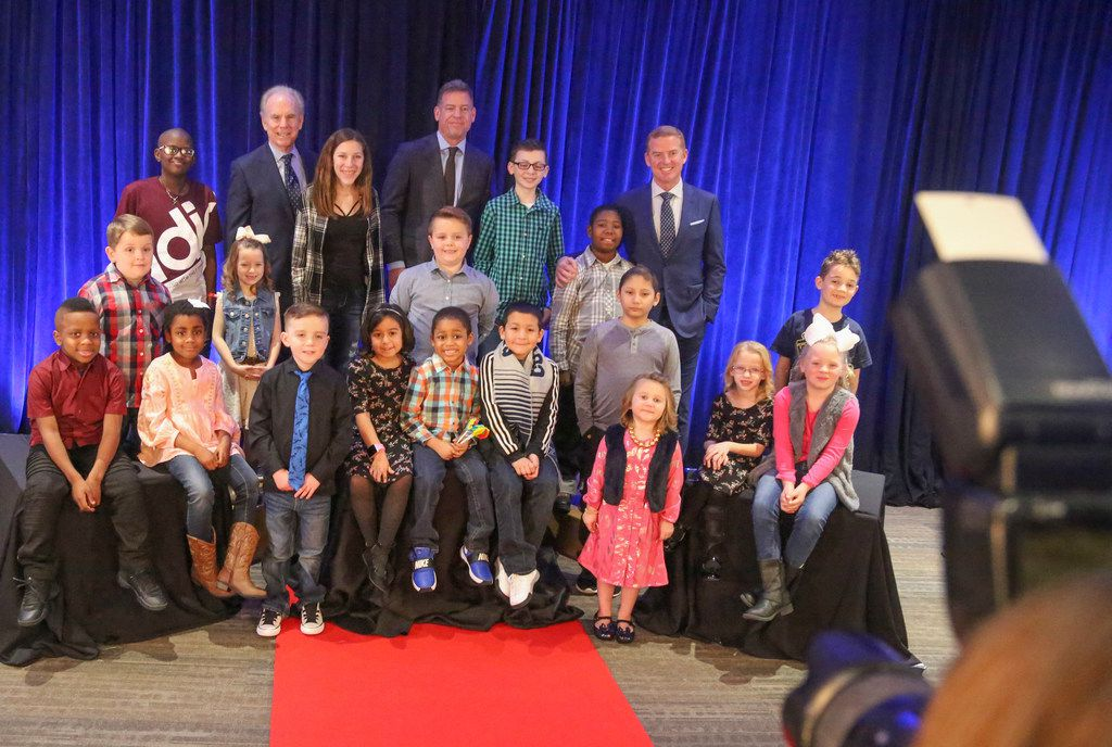 Former Dallas Cowboys quarterbacks Roger Staubach (left), Troy Aikman and current Dallas Cowboys head coach Jason Garrett pose with children who were models for the fashion show portion of The Children Cancer Fund 30th Anniversary Gala during the annual photo shoot at Children's Medical Center Dallas in January 2018. The two former quarterbacks are the honorary chairmen for the event, and Jason Garrett stopped by to show his support.