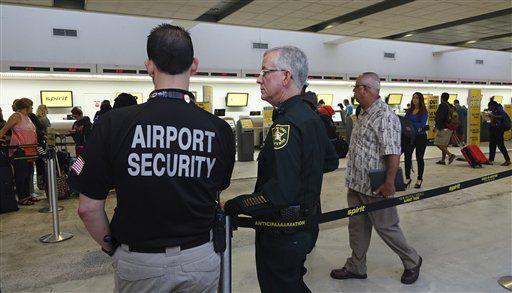 Guardias de seguridad y la policía vigilan la cola en el mostrador de Sporot Airlines, martes 9 de mayo de 2017, en el aeropuerto internacional de Fort Lauderdale, Floridia, donde se produjeron trifulcas entre pasajeros furiosos debido a cancelaciones de vuelos.  (Joe Cavaretta/South Florida Sun-Sentinel via AP)