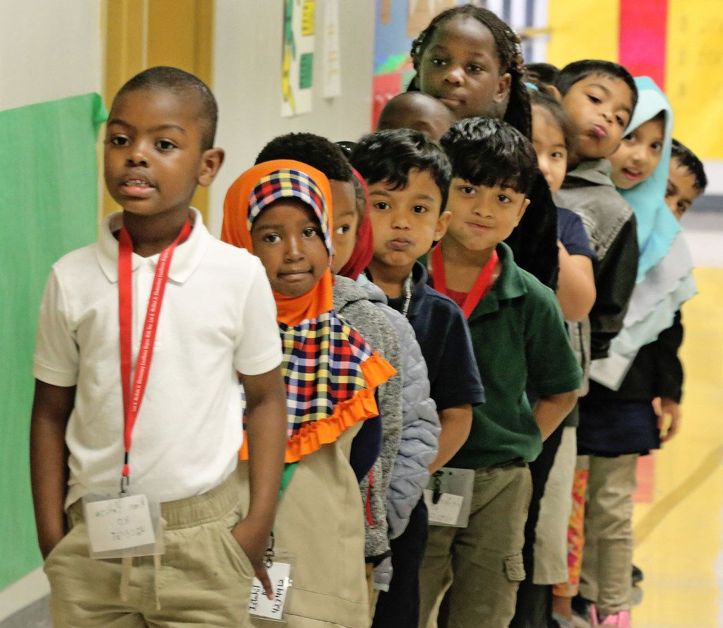 Kim Hakiza, left, leads the line of Adrian Rivera's kindergarten class as they wait in the hallway together at Dallas ISD's McShan Elementary in Vickery Meadow in Dallas, photographed on Dec. 15, 2017. (Louis DeLuca/The Dallas Morning News)