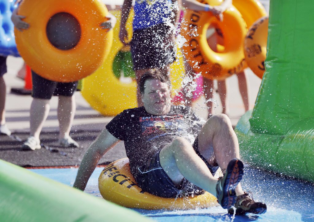 James Rhoads slides down a 1,000 foot water slide during the Slide the City event in the 3400 block of Sylvan Ave. in Dallas, Saturday, June 25, 2016. (Brandon Wade/Special Contributor)