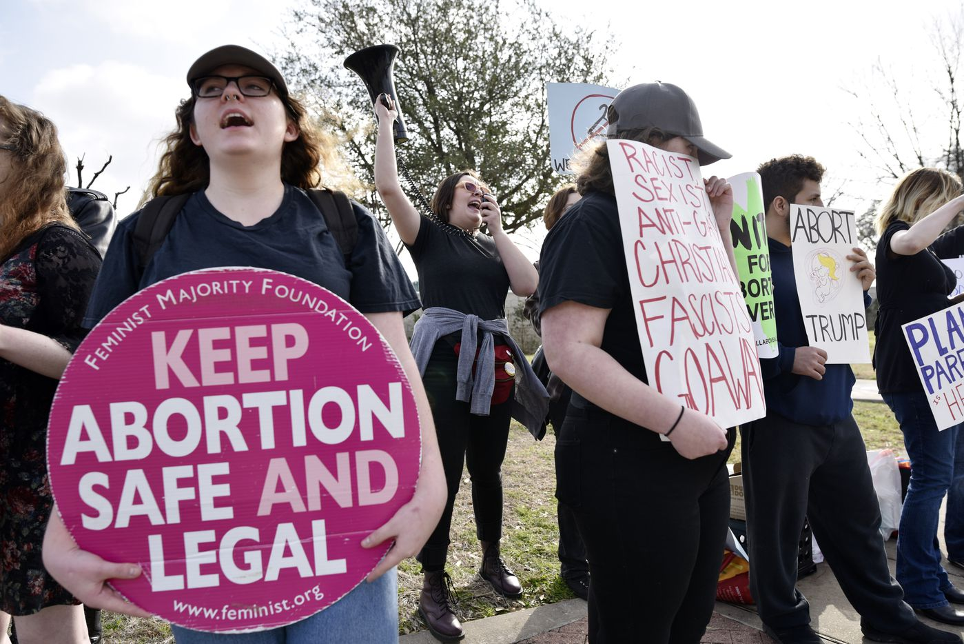 A  coordinator with the Defend Abortion Access Coalition used a megaphone to lead chants Saturday during dueling protests outside of the Planned Parenthood South Dallas Surgical Health Services Center.