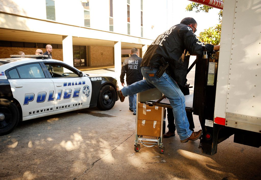 Dallas police officials cart out boxes from a raid on the Catholic Diocese of Dallas.