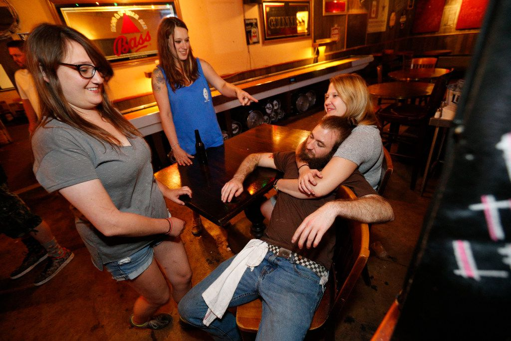 Ryan Sutton, bartender (bottom right) is hugged by his girlfriend Meg McClendon as Holly Terry (left) and Sable Gunter watch after the last shift at Elbow Room in Dallas on April 16, 2017. (Nathan Hunsinger/The Dallas Morning News)