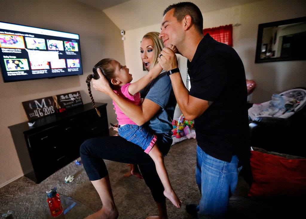 Jayme Magallon supports her 3-year-old daughter Annalynne, who has cerebral palsy, as they play with her husband Brandon Magallon at their Burleson home on Friday, July 13. The Magallons are one of many families who say they've considered divorce so that their sick or disabled children can be cared for through the unemployed parent's Medicaid. The situation is informally advised to many Texas families.