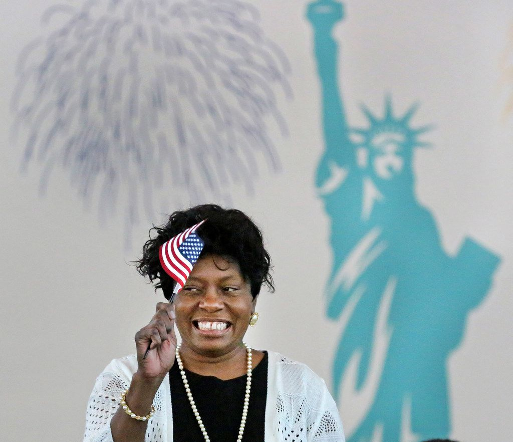 Elizabeth Evans, from Zambia, happily waves a miniature American flag as she becomes an American citizen at a naturalization ceremony in May 2018.