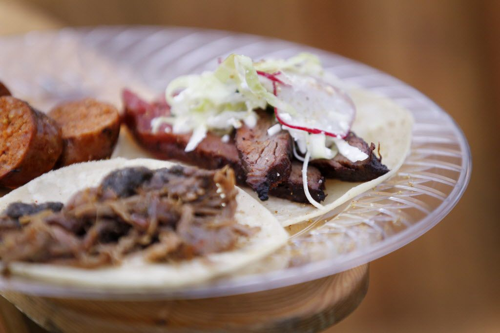 A barbecue dish with pork sausage, goat meat and beef from the tent of Live Fire Pit with chef Tim Byres during the Fork & Cork festival Addison Circle Park