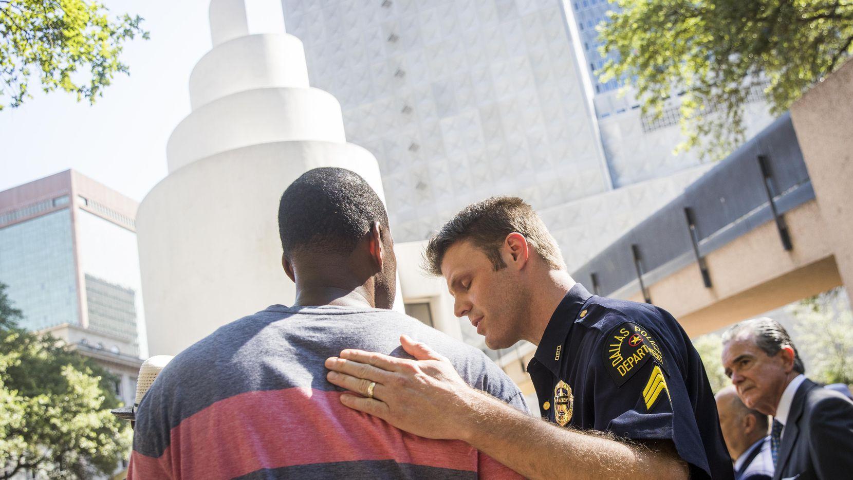 El sargento Dan Mosher abraza a Odell Edwards, el padre de Jordan, un joven de 15 años que murió a manos de un policía de Balch Springs en abril. Ambos participaron en un acto conmemorativo por las víctimas  del 7 de julio del año pasado. SMILEY N. POOL/DMN