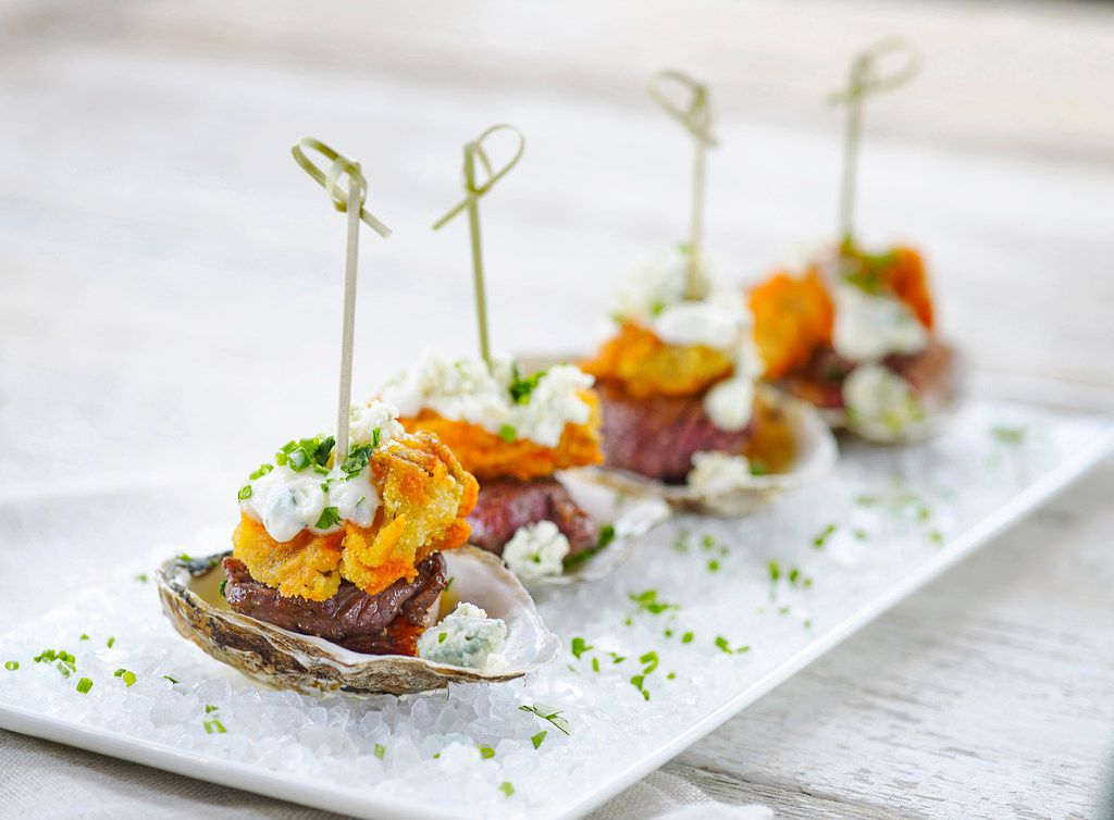 The Carpet Bagger On the Half Shell appetizer from B&B Butchers and Restaurant comes features filet mignon topped with applewood smoked thick-cut bacon, cajun fried oysters, crumbled blue cheese, house-made blue cheese dressing and hot sauce.