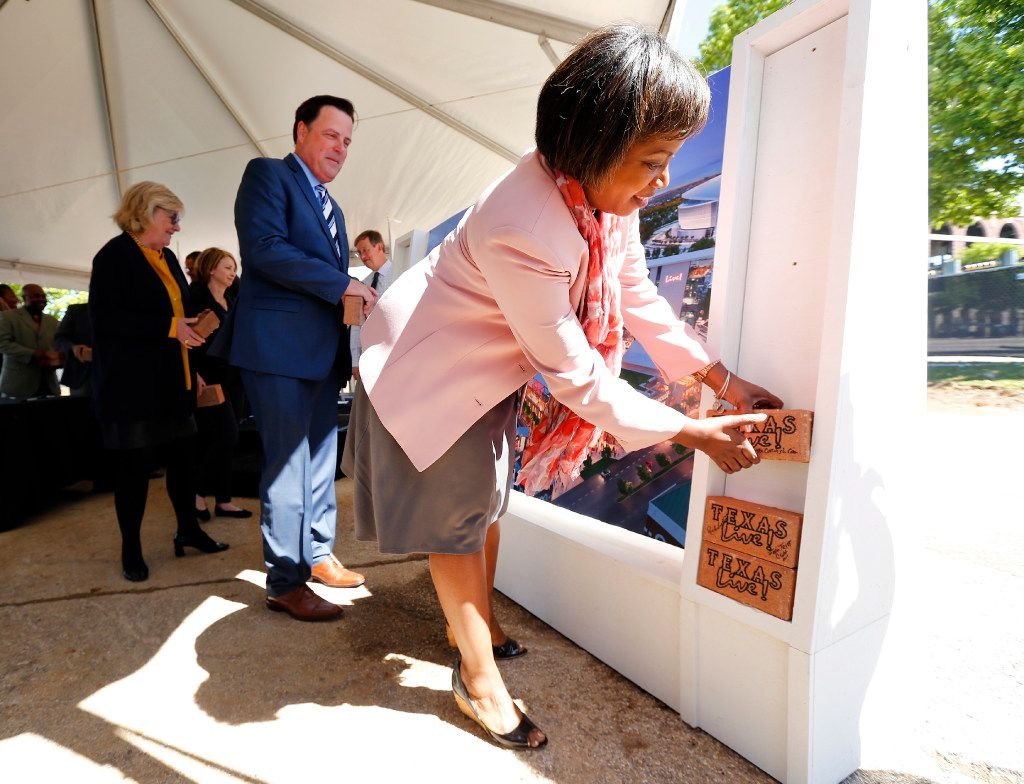 Luwanda Jenkins of The Cordish Companies (right) and Arlington Chamber of Commerce president and CEO Michael Jacobson (middle) place signed bricks in a display during groundbreaking ceremonies for Texas Live! in Arlington. (Tom Fox/Staff Photographer)