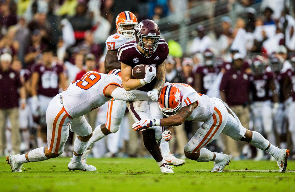 FILE - Texas A&M tight end Jace Sternberger (81) is tackled by Clemson safeties Tanner Muse (19) and Isaiah Simmons (11) during the first quarter of a game on Saturday, Sept. 8, 2018 at Kyle Field in College Station. (Ashley Landis/The Dallas Morning News)