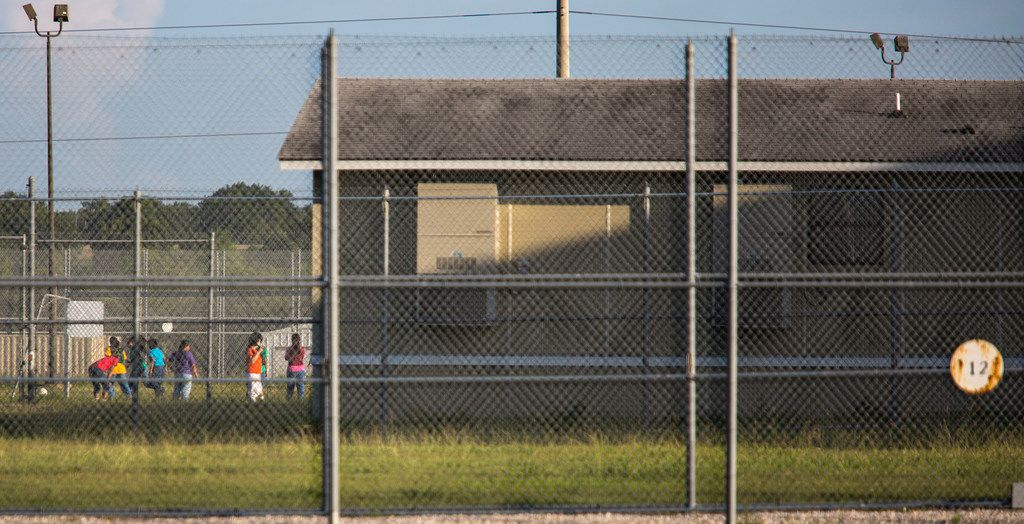 Some people are seen outside in a fenced off yard at the T Don Hutto Residential Center in Taylor, Texas on June 25, 2018. (Thao Nguyen/Special Contributor)