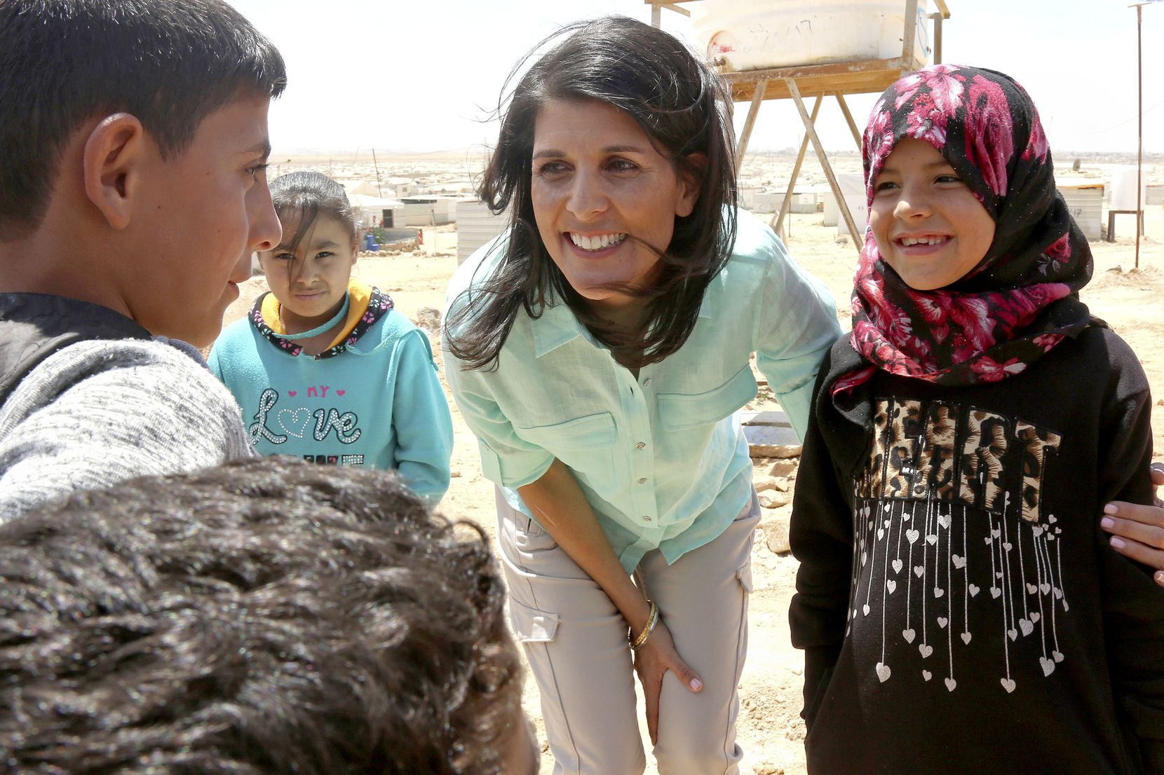 """U.S. Ambassador to the United Nations Nikki Haley, speaks with Syrian refugee children, during a visit to the Zaatari Refugee Camp, Jordan, Sunday, May 21, 2017. Haley said the Trump administration wants to step up help for the millions of people displaced. Yet Nikki Haley's message is at odds with President Donald Trump's """"America First"""" agenda, his planned budget cuts and his hardline position on admitting refugees."""