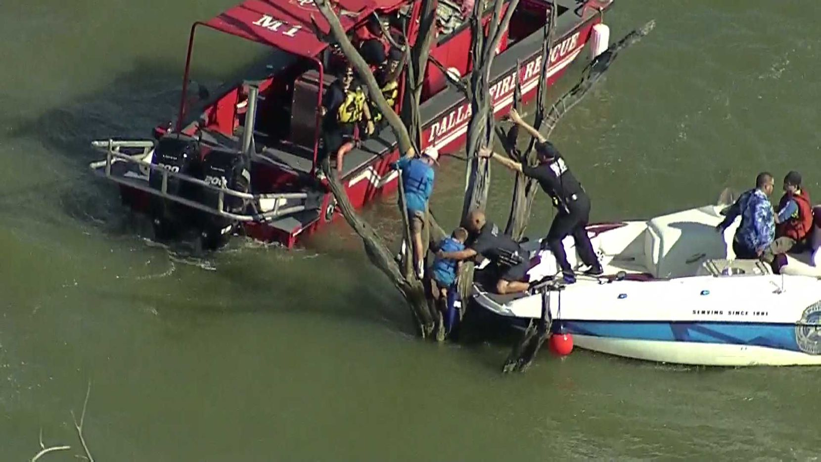 Rescuers from Dallas police and Dallas Fire-Rescue work to free two children stranded in a tree after their boat sank Wednesday in Lake Ray Hubbard.