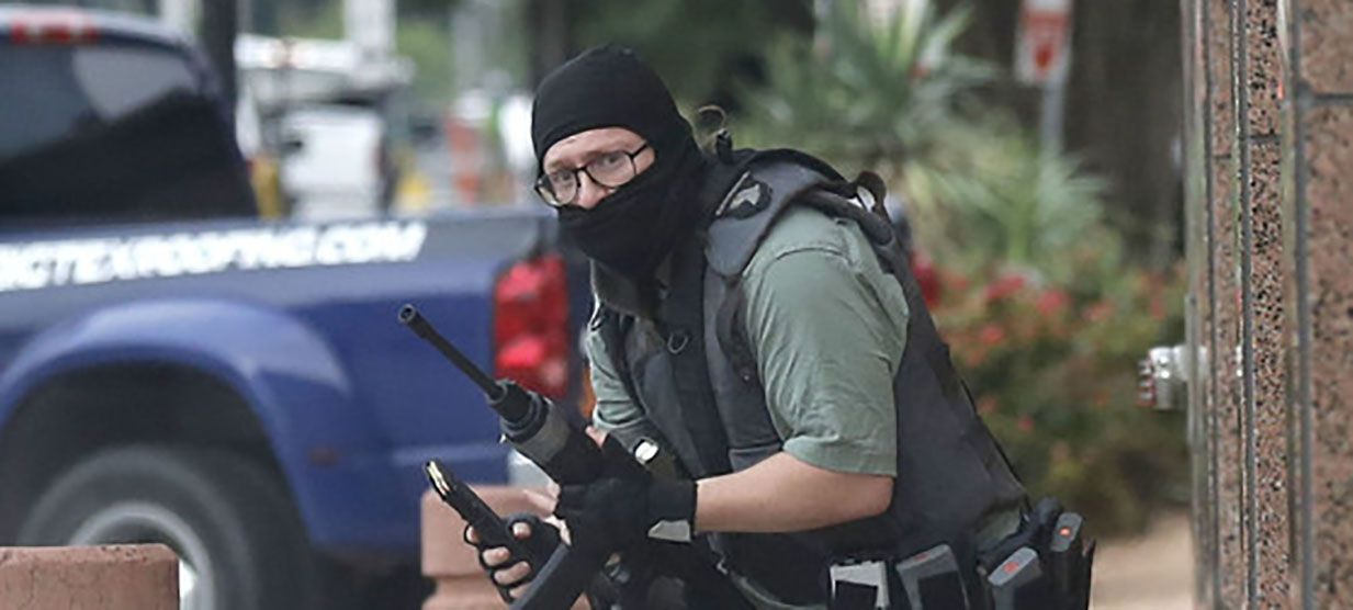 A masked gunman, later identified as 22-year-old Brian Isaak Clyde, makes his way along Jackson Street toward the south entrance of the Earle Cablell Federal Building in downtown Dallas. Dallas Morning News staff photographer Tom Fox, who had been assigned to cover a trial, was waiting to enter the building when Clyde opened fire from across the street.