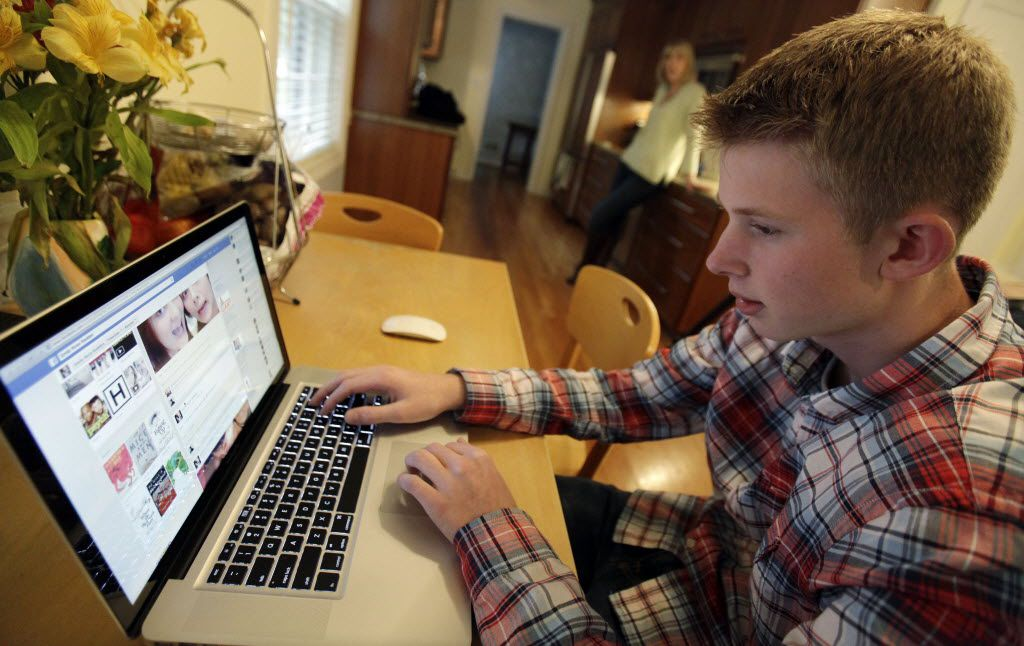 In this Oct. 24, 2013 photo, Mark Risinger, 16, checks his Facebook page on his computer as his mother, Amy Risinger, looks on at their home in Glenview, Ill. The recommendations are bound to prompt eye-rolling and LOLs from many teens but an influential pediatrician's group says unrestricted media use has been linked with violence, cyber-bullying, school woes, obesity, lack of sleep and a host of other problems. Mark'€™s mom said she agrees with restricting kids'€™ time on social media but that deciding on other media limits should be up to parents. (AP Photo/Nam Y. Huh)